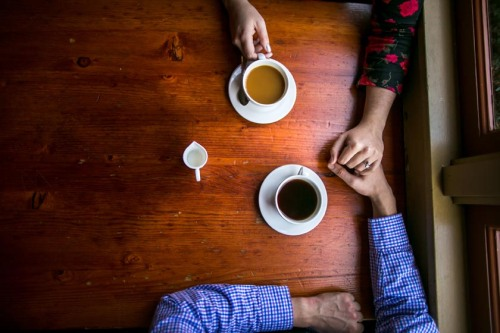 couple holds hands at restaurant
